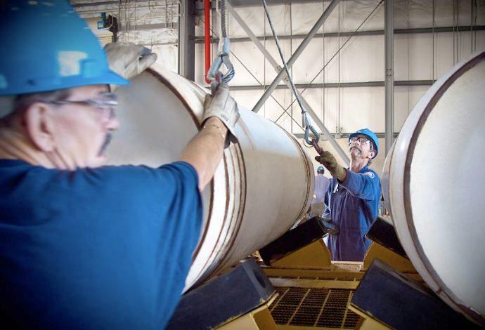 Workers unloading a cylinder of uranium hexafluoride
